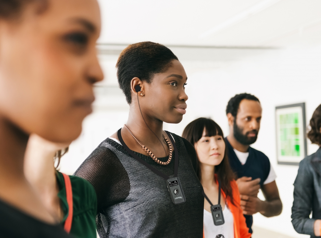 Mixed group of visitors standing and listening during a gallery opening in Berlin, Germany. Focus is on a young black african woman smiling and wearing earbuds. Horizontal shot of people with artwork in the background hanging on the wall.