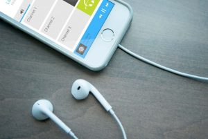 Portion of a smartphone with the Listen EVERYWHERE app with ear buds plugged into the phone