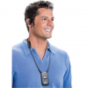 Middle-aged man with dark hair wearing a short sleeved, blue collared polo shirt, smiling while wearing over-the-ear headphones and a black receiver hanging from a lanyard around his neck