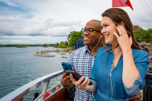 Couple on boat tour listening to audio through smartphone