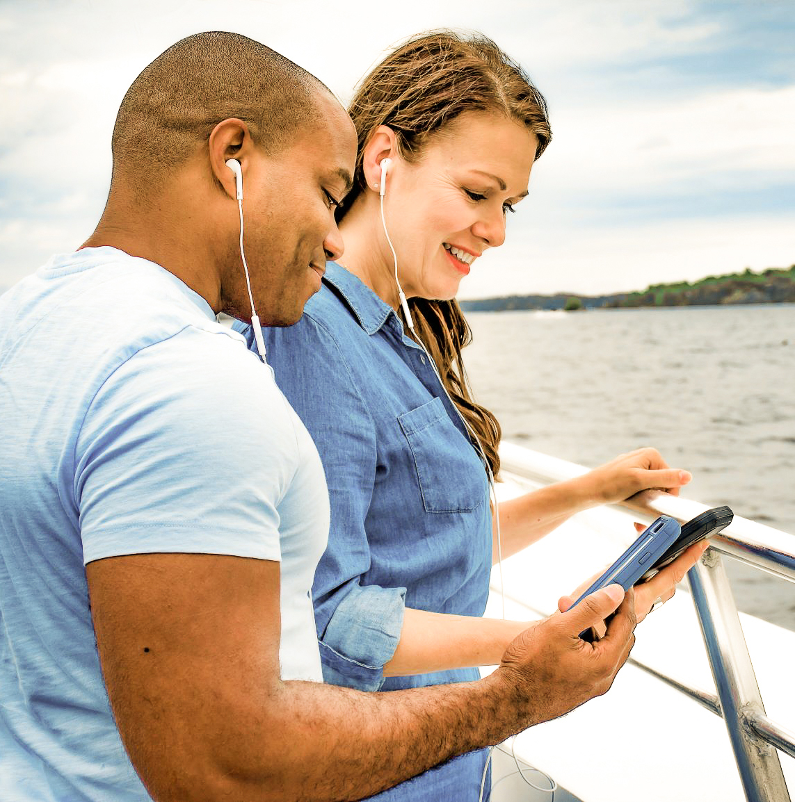 Couple on boat tour listening to audio through smartphone and earbuds
