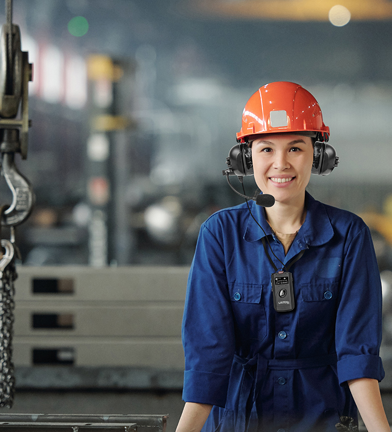 Cheerful young woman in workwear and protective helmet looking at you
