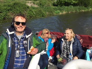Three people with assistive listening devices on a river tour