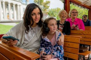 Young dark-haired woman and her daughter about 8 or 9 listening to audio with different headsets, sitting on a tour trolley with wooden benches, open air sides, and other tourists, two older women, laughing in the background.