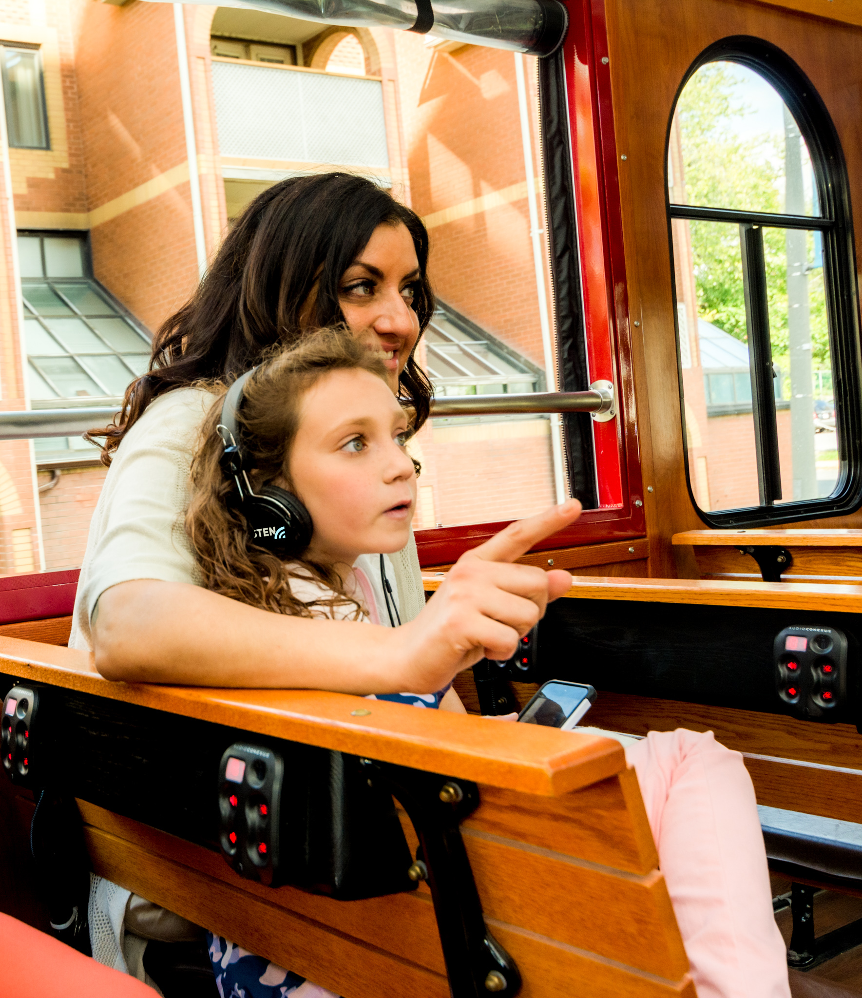 Mom and daughter with headphones on trolley tour