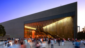 The outside of Abravanel Hall during sunset with lots of people gathered outside the building