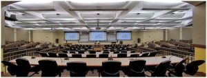 Large classroom, well lit, with tables and chairs in rows, three large video monitors at the front of the room.
