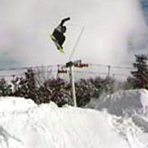 Snowboarder flying over snow somewhere in deep snow with the lift in the background