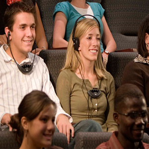 Two smiling people using headphones and assistive listening devices during a church service