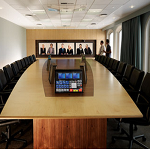 Conference room with 2 people there and 6 people shown meeting virtually through a screen