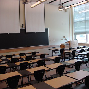 Empty classroom showing desks, chairs, a bright window with the shade partially down, fluorescent lighting, AV cameras and projectors installed on the ceiling and the wall, a long chalkboard, and a teaching pulpit.