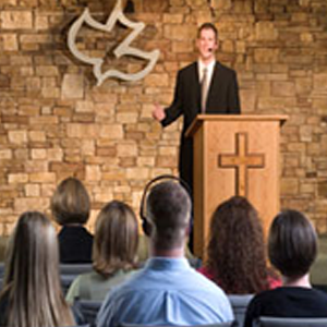 Man speaking to congregation in a church setting