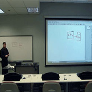 Classroom view from a students perspective with a teacher/presenter at the front of the classroom with a screen projector displayed