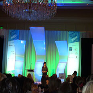 A woman on a brightly lit stage at the women in tech council