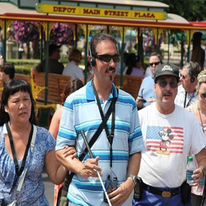 People using assistive listening on a tour in Disneyland