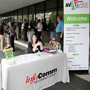 Welcome table with a white tablecloth with InfoComm International printed on the front. The Pull-up banner located on the right says AV Week, Welcome, with smaller unreadable text. Friendly smiling woman sitting at the table with wandering crowds of people in the background.