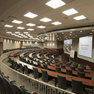 Empty college classroom with several rows of tables and chairs