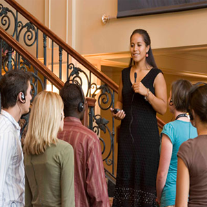 A woman in a black sleeveless dress standing on a staircase with elaborate iron work is speaking into a microphone to a group of people using headphones