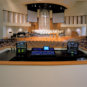 Soundboard equipment overlooking house of worship sanctuary with lights on but no audience