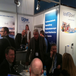 Busy tradeshow floor with groups of people standing and other groups sitting at a Listen Technologies booth