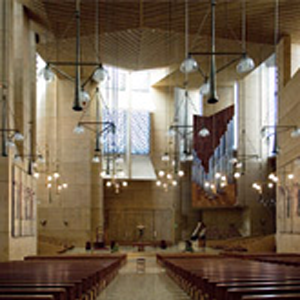 Cathedral of Our Lady of the Angels Sanctuary high ceilings, rows of empty pews, unique hanging geometric shaped light fixtures with large stain glassed windows