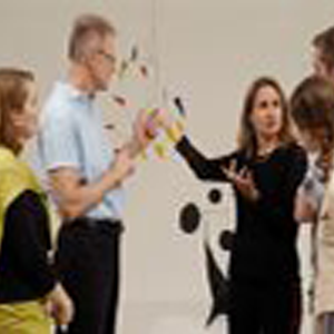 Woman presenting to group at art exhibit