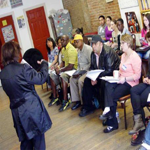 A group of people seated in a room intently listening to a leader or person in charge who is explaining something to them, there are several women and men all different ages.