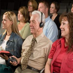 Group of people sitting as an audience with an older gentleman in a dress shirt and a tie, wearing a headset and holding an assistive listening receiver in his hand