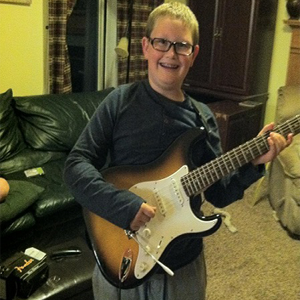 Boy smiling holding a guitar in his living room