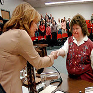 Brown-haired woman in suit jacket is shaking the hand of a young woman in a collared dress shirt and button-down sweater vest