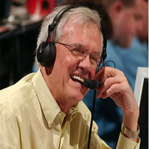 """Close-up photo of Rodney Clark """"Hot Rod"""" Hundley with a big smile and wearing a long-sleeved soft yellow button-down dress shirt, his wire frame oval shaped glasses, and a headset with a microphone"""