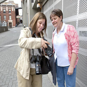 Two tourists outside while looking at the digital display of a camera to look at what was just photographed.