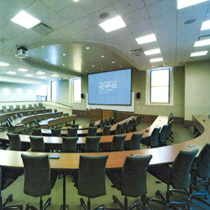 Aerial view of an empty college classroom with empty tables and chairs with a large projector display