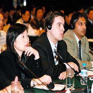 People of different nationalities sitting wearing headsets listening to someone speak at a conference center