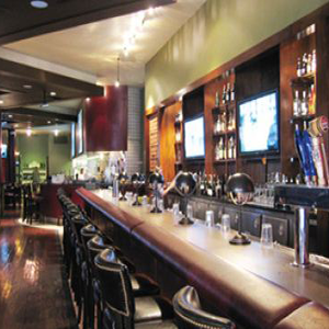 Bar with TVs behind it