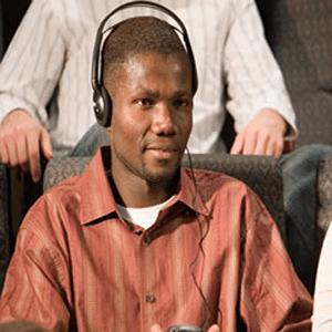 Man sitting using assistive listening device