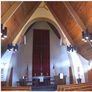 The view of a church sanctuary with a large cross on the wall behind a pulpit with two flags on either side, empty pews, and vaulted ceilings