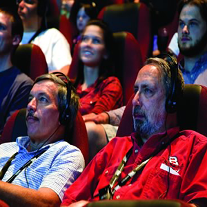 Men using assistive listening devices to watch a movie
