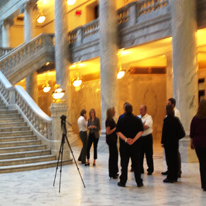 Inside the Utah State Capitol Building with marble flooring, marble staircase, and large marble pillars with a group of people standing around what appears to be a camera mounted on a tripod