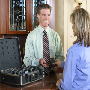 Smiling employee handing a woman an assistive listening device