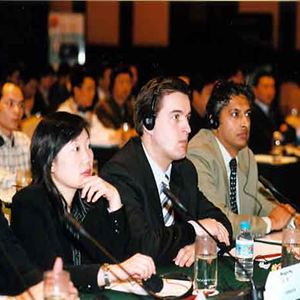 a group of people in a room paying attention with the focus on three people seated at a long table with microphones in front of them, two are wearing headsets.
