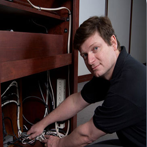 Brown-haired, blue-eyed 30-something man wearing a short-sleeved, black polo, squatting with both hands on wires in a nicely finished wooden shelving unit, looking at the camera.