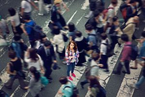 Young woman feeling isolated in a busy crowd in the city
