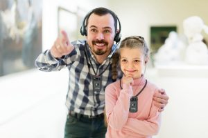 Father and daughter walking through gallery with assistive listening devices