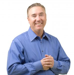 headshot image of our Founder, Russ Gentner with him smiling while pressing his hands together