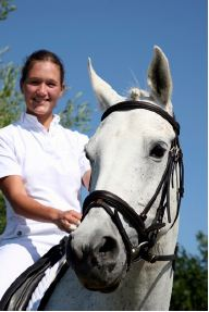 Cloe up of a young woman with long brown hair that's pulled back, wearing a white short sleeved button-down top, riding a white horse with a black bridle.