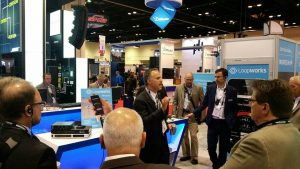 A shot of a man on a tradeshow floor, speaking to a group of men wearing devices on lanyards around their necks with trade show booths all around them