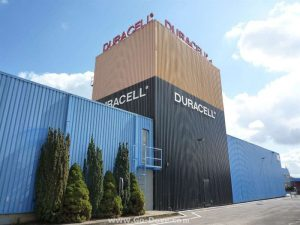 Large blue metal building with the center of the building taller and painted to look like a Duracell battery