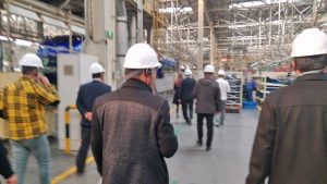 Shot of a widespread group of men walking away in hardhats, and street clothes in a production facility with high ceilings and shelving units