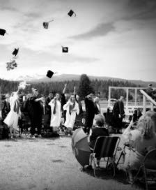 Grayscale photo of a group of high school graduates standing outside and throwing their caps in the air in celebration in front of a group of people in chairs